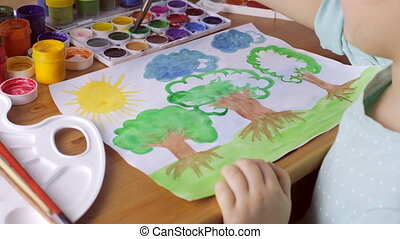 Cute young girl draws brown trees with green leaves on white paper