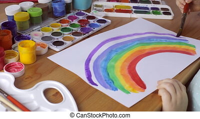 Cute young girl draws colored rainbow on white paper