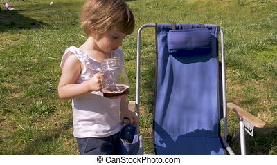 Cute young girl holding a glass mug with juice outside next to a lawn chair