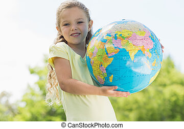 Cute young girl holding globe at park