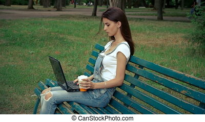young girl holds a laptop on your legs in the Park and drink coffee
