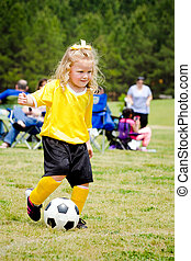 Cute young girl in uniform playing in organized youth league soccer game