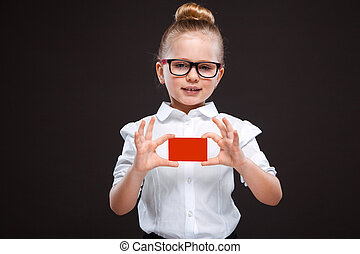 Cute young girl in white shirt and black trousers hold red card