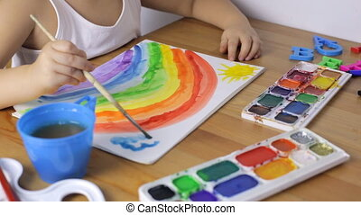 Cute young girl is drawing rainbow