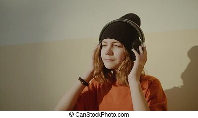 cute young girl listening music in headphones and dancing, ...