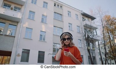 cute young girl listening music in headphones, urban style, stylish hipster teen choosing track on mobilephone and smile infront of oidsity buildings, orange crazy street style