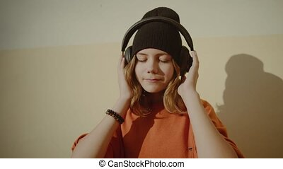 cute young girl listening music in headphones, urban style, ...