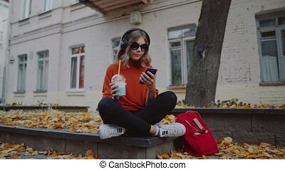cute young girl listening music in headphones, urban style, stylish hipster teen sitting on a sidewalk on city street and choosing track on mobilephone infront of oldcity buildings, orange street style