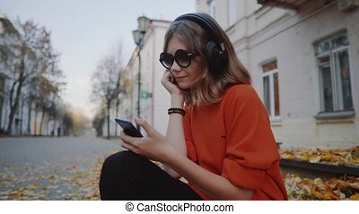cute young girl listening music in headphones, urban style, stylish hipster teen sitting on a sidewalk on city street and choosing track on mobilephone infront of old city buildings, orange street style