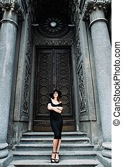 Cute young girl modeling appearance posing against the backdrop of huge beautiful doors in black dress and hat