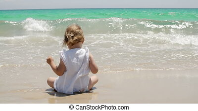 Cute young girl paddling in the surf