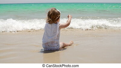 Cute young girl paddling in the surf sitting on the sand at...