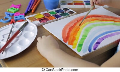 Cute young girl painting a colored rainbow. Close up