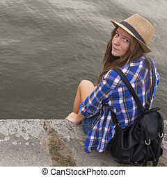 Cute young girl sitting on a stone embankment of the river.