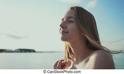 Cute young girl sitting on the seashore watching the setting...