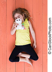 Cute young girl sleeping with her plush toy cat