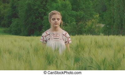 Cute young girl walks in the field of the green wheatfield. Slowly