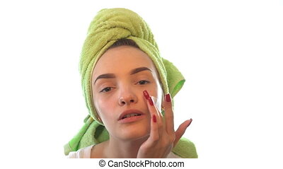 young girl with a towel on head gently causing the cream on her face