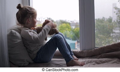 Cute young girl with toy sitting on a window sill