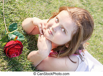 lying girl on grass with rose