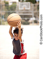 Cute young kid holding basketball
