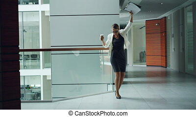 Cute young lady manager is dancing in hall of business...