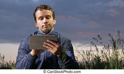 Cute young man working on a tablet computer at sunset on the field. Beautiful sky on a background.