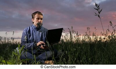 Cute young man working on laptop at sunset on the field. Beautiful sky on a background.