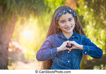 Cute Young Mixed Race Girl Making Heart Hand Sign Outdoors