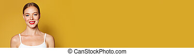 Cute young model woman on bright yellow banner background with copy space