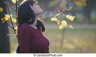 Cute young pregnant woman standing at autumn park among golden leaves, looking at sky
