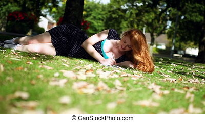 Cute young redhead doing assignments lying on green lawn