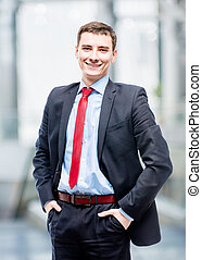 Cute young successful businessman in office posing