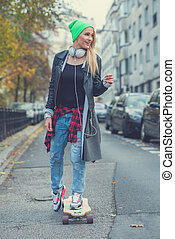 Cute young urban woman using a skate board