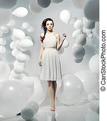 Cute young woman among numerous balloons