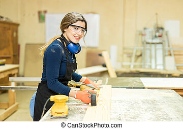 Cute young woman doing some woodwork