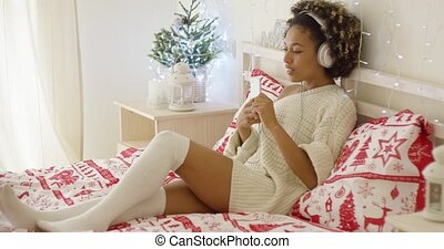 Cute young woman enjoying her music at Xmas lying on her bed...