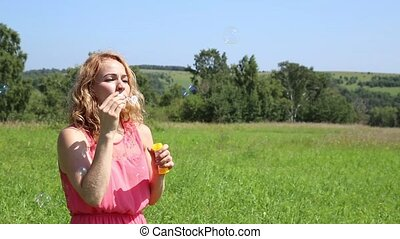 Cute young woman having fun with bubbles, she blowing bubbles