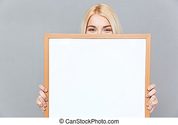 Cute young woman hiding her face behind blank white board