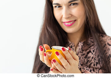 Cute young woman holding a small toy yellow mug in her hands posing on a white background. Favorite drinks concept