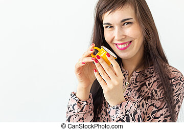 Cute young woman holding a small toy yellow mug in her hands posing on a white background with copy space. Favorite drinks concept