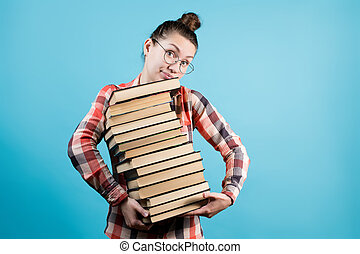 Cute young woman holds a high stack of books