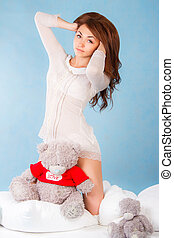 Cute young woman in a bed with a teddy bear over cyan...