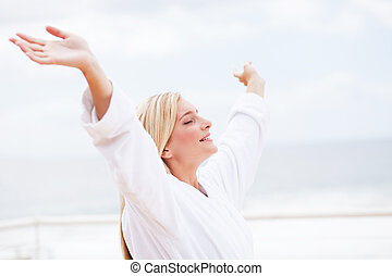 cute young woman in bathrobe with her arms opened in the morning