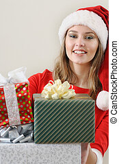 cute young woman in Santa hat with gifts for Christmas looking at camera