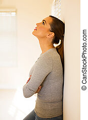 young woman leaning against the wall