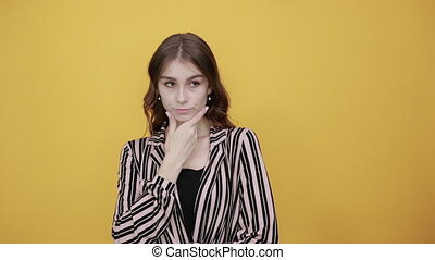 Cute Young Woman Light Brown In Striped Pink, Black Shirt On A Yellow Background, Confident Girl Looks Forward, Touches Chin With Her Hand. The Concept Of Business People And Leadership.