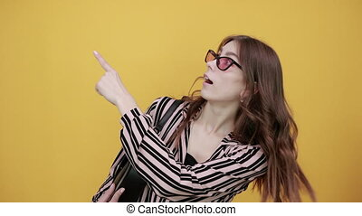 Cute Young Woman Light Brown In Striped Pink, Black Shirt On A Yellow Background, Happy Girl With Sunglasses And Bag Smiles, Shows Direction With Forefinger