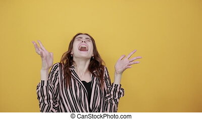 Cute Young Woman Light Brown In Striped Pink, Black Shirt On A Yellow Background, Irritated Girl Is Nervous, Screams, Fingers Spread Wide. Concept Of Human Emotions And Relationships