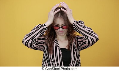 Cute Young Woman Light Brown In Striped Pink, Black Shirt On A Yellow Background, Upset Girl In Sunglasses Holding Her Hands To Forehead From Head Pain, Headache
